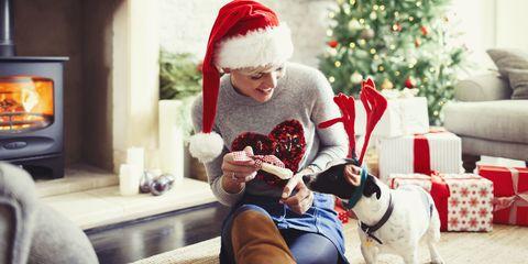 Woman giving bone to dog wearing Christmas reindeer antlers