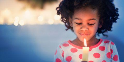 Child holding candle Christmas pyjamas