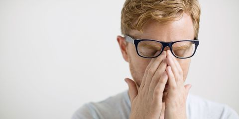 Tired man wearing glasses rubbing his eyes