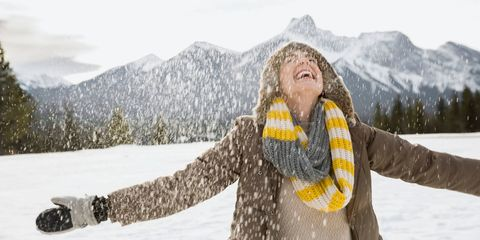 Snow falling around happy woman with arms outstretched