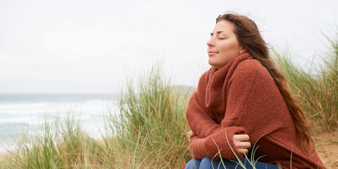 Woman sitting with eyes closed at beach.