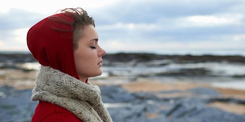Woman in winter wearing red coat on coast line beach by the sea