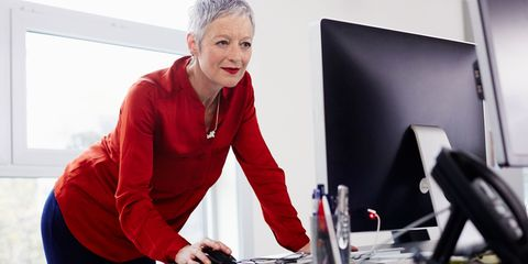 Woman standing up at desk to do her work