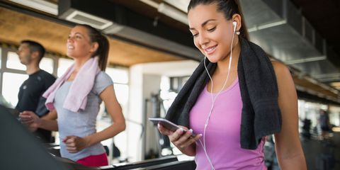 Young woman using mobile phone while exercising on treadmill