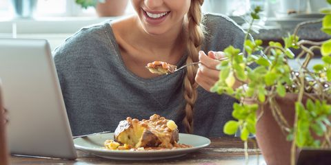 Woman at home eating jacket potato