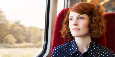 Woman with red hair looking out of window on train