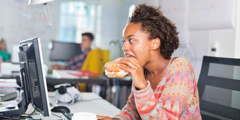 Woman eating sandwich at desk