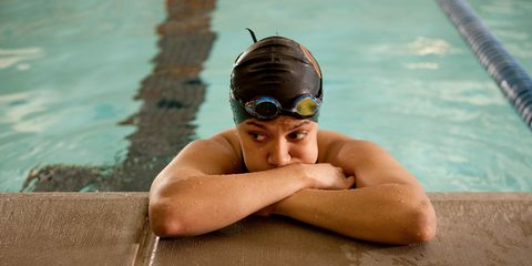 Unhappy swimmer leaning at edge of pool