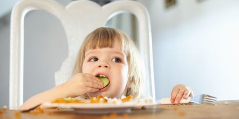 Little girl eating cucumber and fish fingers