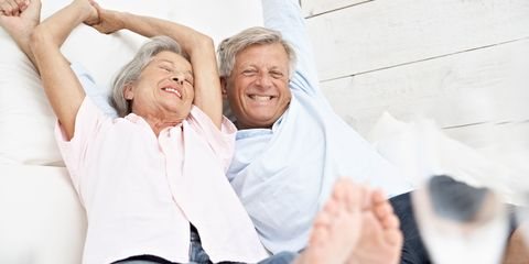 Senior couple in bed smiling