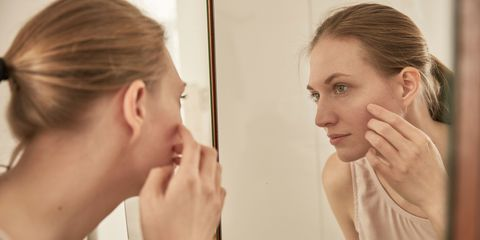 Woman looking in mirror self-examination