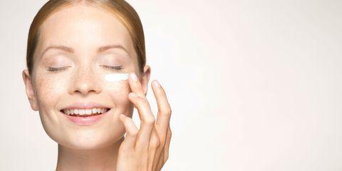 Young woman applying mosituriser under eye