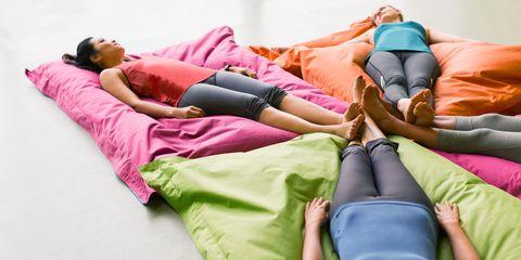 Women laying on cushions in restorative yoga gym studio