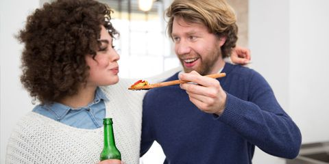 Couple cooking in kitchen tasting food