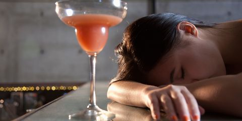 Woman asleep at the bar next to a full cocktail