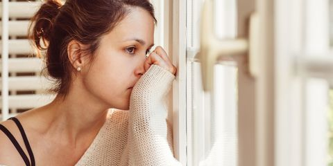 Anxious woman looking out of window