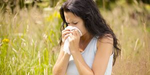 Woman with hay fever blowing her nose surrounded by pollen