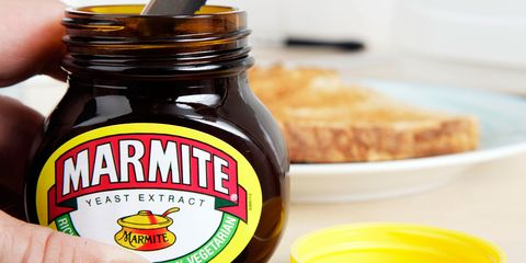 A man getting Marmite out of the jar with a knife