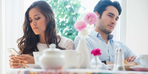 Unhappy couple ignoring each other in a cafe