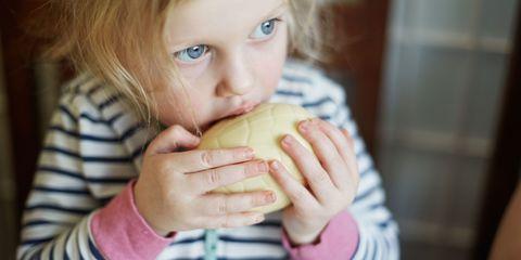 Little toddler girl enjoying eating a white chocolate Easter egg
