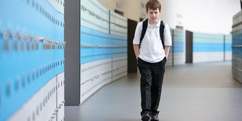 Unhappy schoolboy walking alone in school corridor