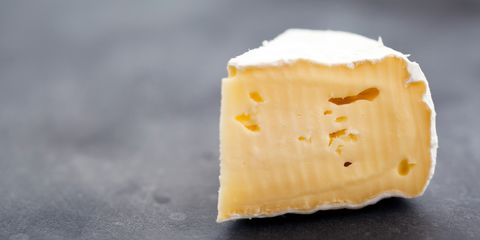 Block of brie cheese on table