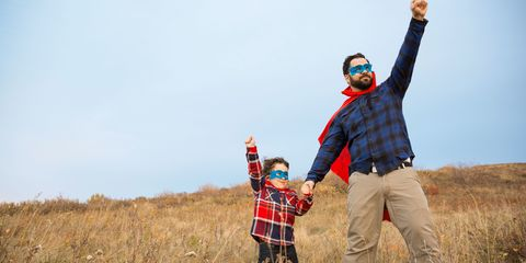 Father and son in superhero capes in field