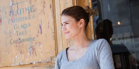 Woman sitting outside a french cafe wearing a grey jumper