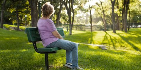 Rear view of mature woman sitting on park bench