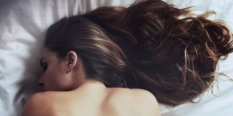 Back view of woman sleeping naked in bed