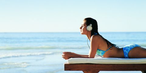 Woman on sun lounger on holiday listening to music