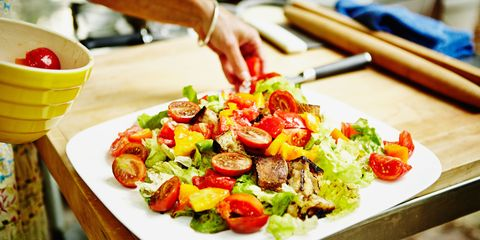 Woman placing heirloom tomatoes on plate of grilled panzanella salad