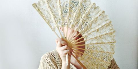 Young woman fanning self in the heat