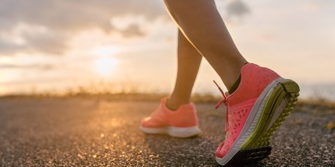 Woman wearing trainers running sunset