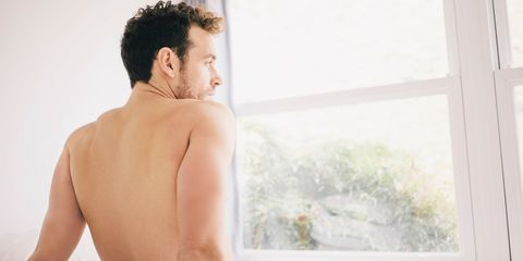 Naked man looking out of window