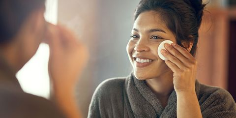 Shot of a smiling young woman taking care of her skin at home