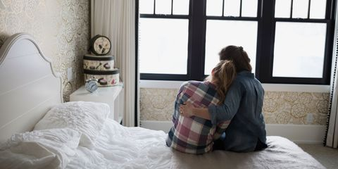 Mother and daughter sat together hugging
