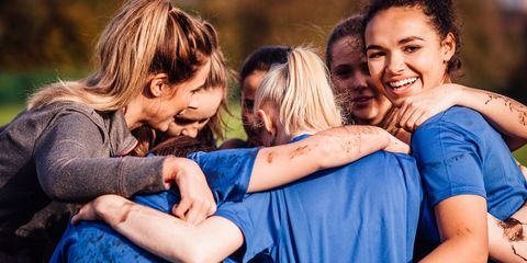 Young teenage girls smiles as she gathers around with her team mates for a chat during their rugby game