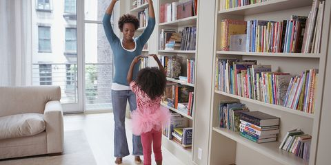 Mother and daughter practicing ballet in living room by bookshelf