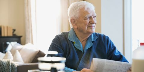 Elderly man with newspaper sitting at breakfast table