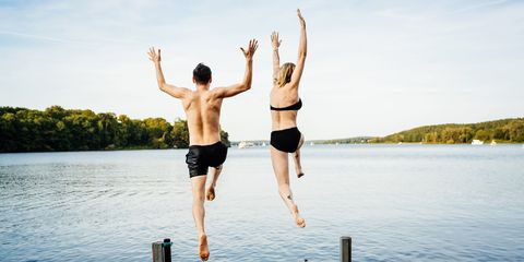 Couple jumping off jetty into water