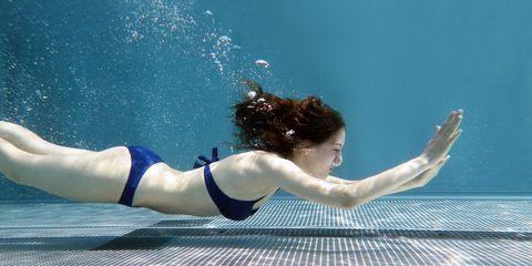 Woman swimming underwater in pool