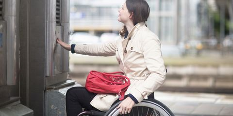 Disabled woman in wheelchair pressing button for lift