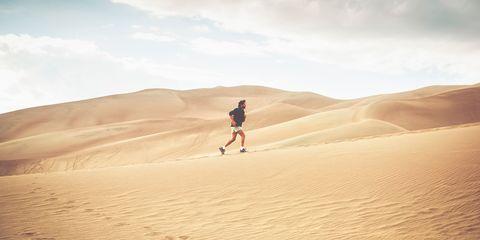 man running on sand dune
