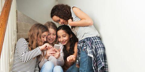 Girls gathered around smartphone on stairs