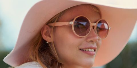 Young blonde woman wearing pink sunglasses and sunhat