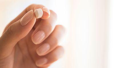 Hand holding vitamin d supplement