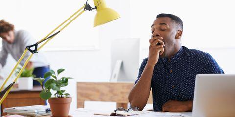 Man yawning at his work desk