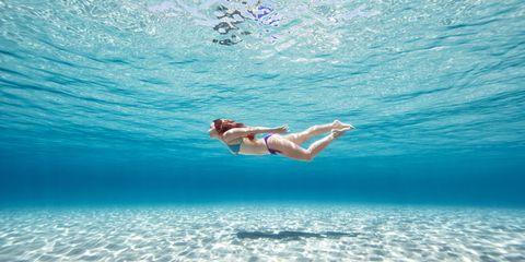 Woman swimming underwater in bikini