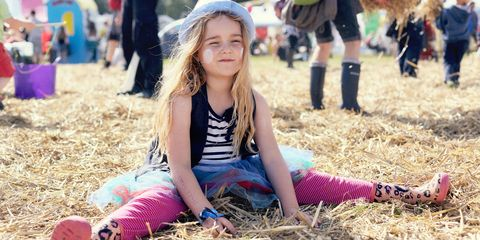 Young girl with long blonde hair wearing leopard print wellies at a music festival sitting on the ground